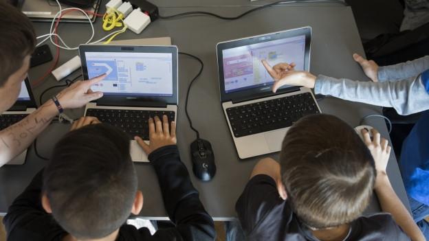 Kinder sitzen an Computer
