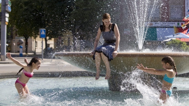 Eine Frau sitzt durchnässt auf einem Brunnenrand, zwei Mädchen spielen im Wasser