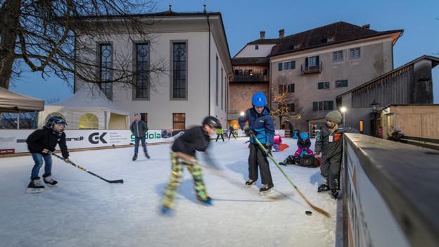 Kinder spielen in der Dämmerung Eishockey im Hintergrund das Schloss