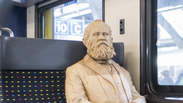 Escher sitzt im Zug