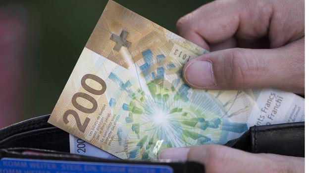 Eine Hand zieht eine 200-er-Note aus einem Portemonnaie.