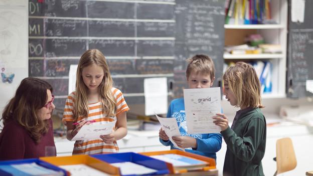 Blick in ein Schulzimmer mit Kindern und einer Lehrerin, die am Pult sitzt.