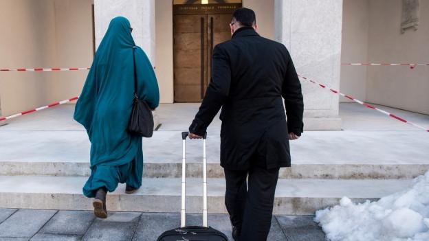 eine verschleierte Frau und ein Mann mit Rollkoffer gehen auf eine Tür zu
