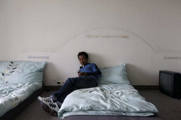 Ein Asysluchender sitzt auf einem Bett