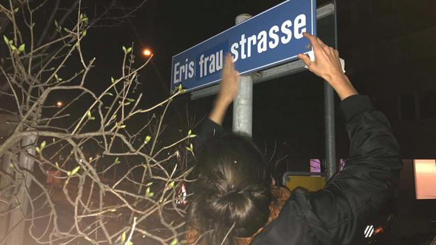 Eine Gewerkschafterin der Unia überklebt in Zürich ein Strassenschild.
