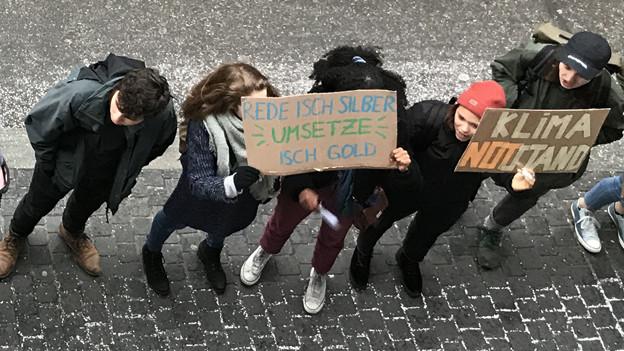 Junge Leute halten ein Transparent mit ihrer Forderung.