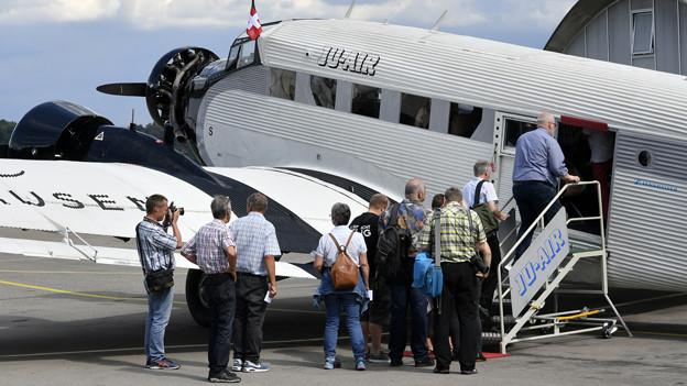 Passagiere steigen in ein Flugzeug der Ju-Air ein.