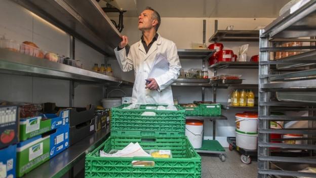 Mann in weissem Kittel im Lebensmittellager eines Restaurants