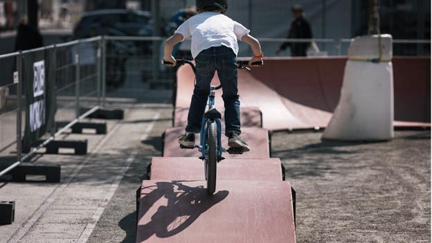 Ein Jugendlicher fährt mit einem Bike über Wellen einer Pumptrack-Anlage.
