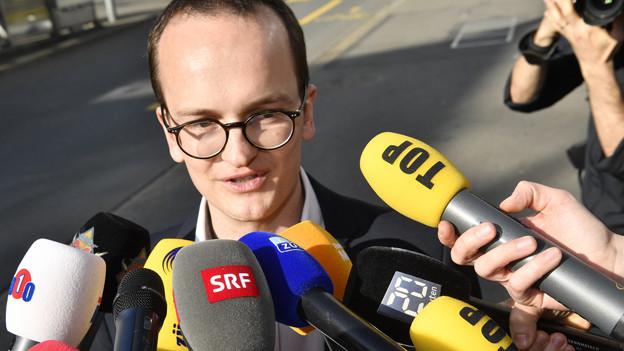Der frisch gewählte Martin Neukom mit zahlreichen Mikrofonen.