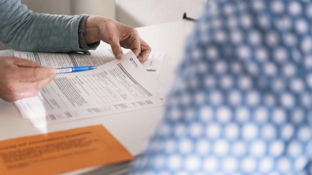 Eine Person füllt einen Antrag für Sozialhilfe aus.