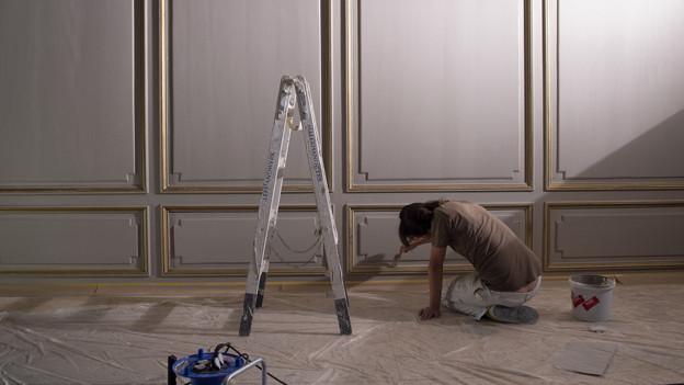 Ein Maler bearbeitet eine getäferte Wand, neben ihm eine Bockleiter