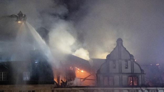 Feuerwahrmann spritzt Wasser in den Brandherd eines Gebäudes beim Hauptbahnhof Zürich