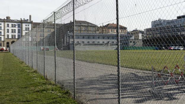 Blick durch den Zaun über die Kasernenwiese auf die Kaserne der Kantonspolizei und das Polizeigefängnis.