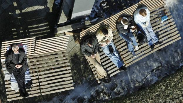 Ausflüglger geniessen auf Holzliegestühlen auf dem Uetliberg die Frühlingssonne.