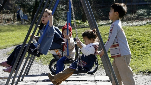 Kinder spielen auf einem Spielplatz.