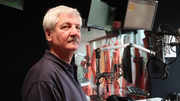 Mann mit grauen Haaren steht im Radiostudio vor Mikrofon