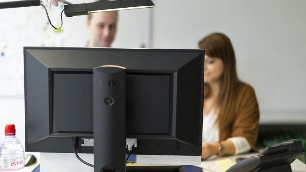 Zwei Mitarbeitende besprechen sich an einem Schreibtisch, im Vordergrund ein Computer.