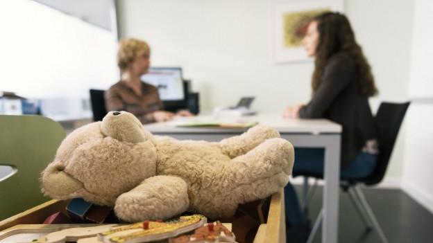 Ein Teddy liegt auf einer Kiste, im Hintergrund führen zwei Frauen ein Beratungsgespräch