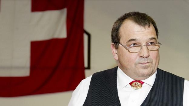 Brustbild Ernst Schläpfer, im Hintergrund eine Schweizerfahne