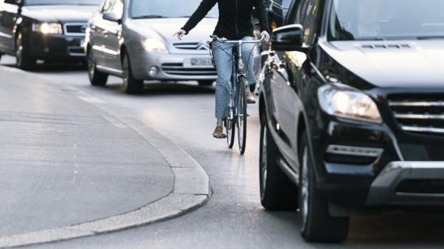 Eine Velofahrerin, eingeklemmt zwischen Autos und Strassenrand