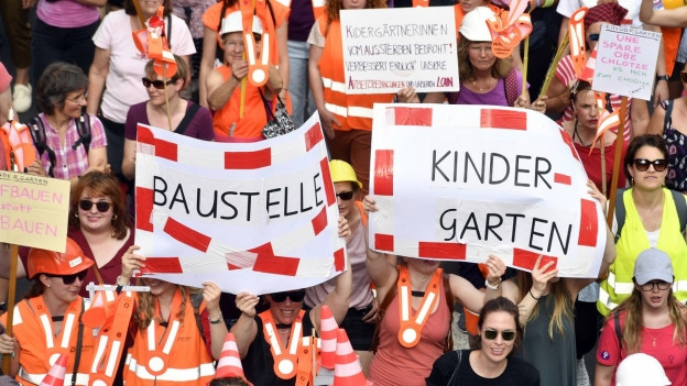 Frauen in orangen Baugewändern halten an der Demo zum nationalen Frauenstreiktag in Zürich Transparente in die Höhe mit der Aufschrift: «Baustelle: Kindergarten.»