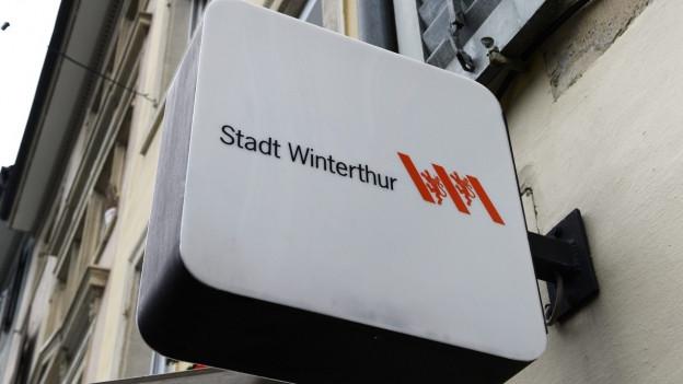Ein weisses Schild an einem Haus, worauf «Stadt Winterthur» steht.