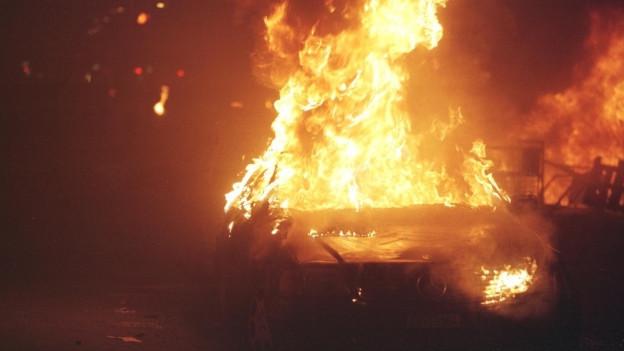Bei einer WEF-Demonstration in Zürich brennt ein Auto.