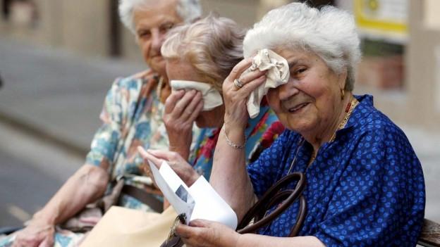 Drei ältere Frauen sitzen auf einer Bank und tupfen sich den Schweiss von der Stirn.