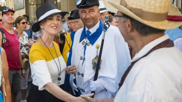 Eine Frau mit Hut begrüsst einem Mann mit Hut inmitten von Leuten.