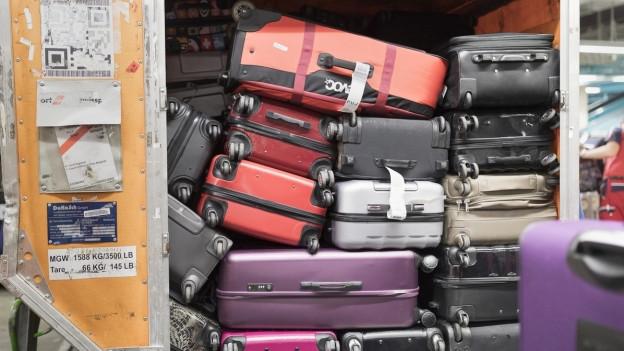 verschiedene farbige Koffer in einem Gepäckwagen