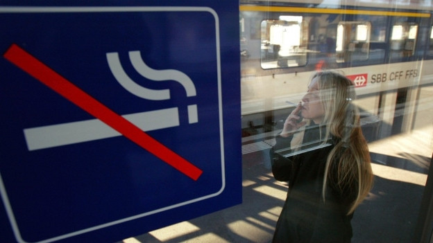 Eine Frau raucht eine Zigarette neben einem wartenden Zug