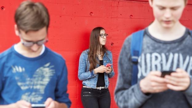 Jugendliche tippen auf ihre Smartphones