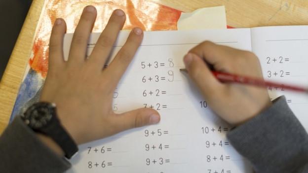 Kinderhände halten einen Bleistift über einem Rechenheft