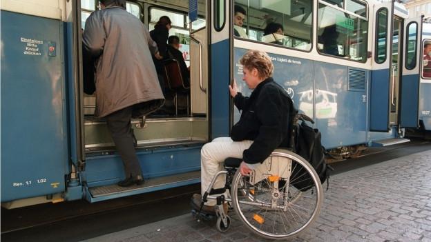 Frau im Rollstohl vor dem steilen Einstieg in ein altes Tram.