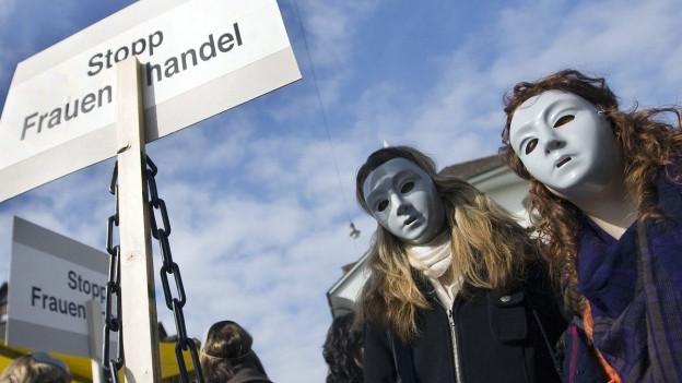 Demonstrantinnen mit weisser Maske prangern Frauenhandel an.