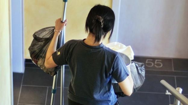 Eine Frau reinigt eine Treppe