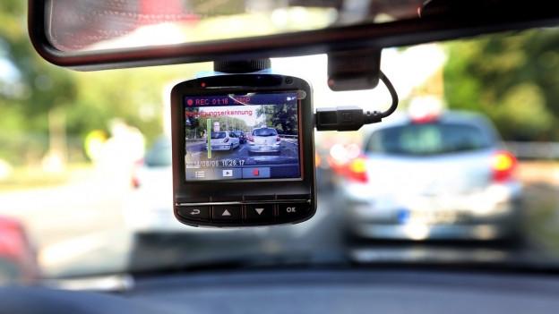 Eine Videokamera filmt durch die Windschutzscheibe den Verkehr vor dem Auto