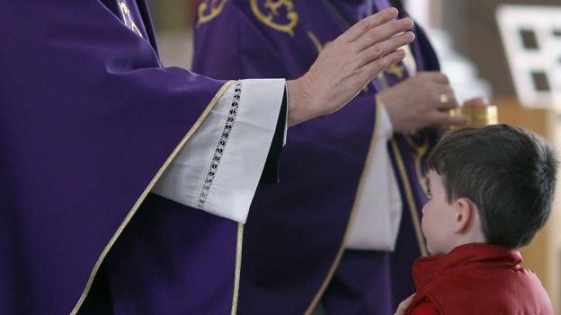 Ein Priester weiht einen kleinen Jungen.