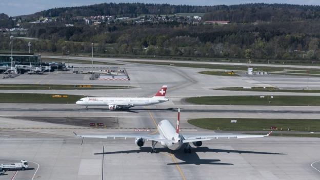 Zwei Flugzeuge stehen auf dem Flughafen Zürich auf der Piste.