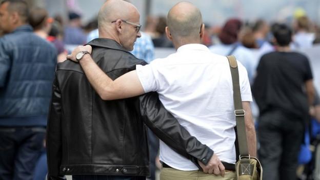Zwei schwule Männer halten sich im Arm.