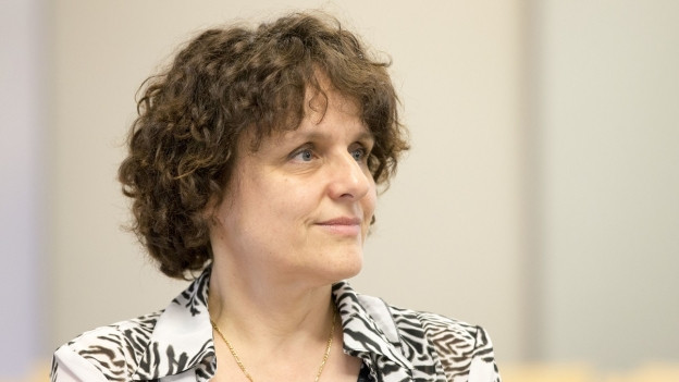 Eine Frau mit lockigem Haar blickt zufrieden in einen Saal.