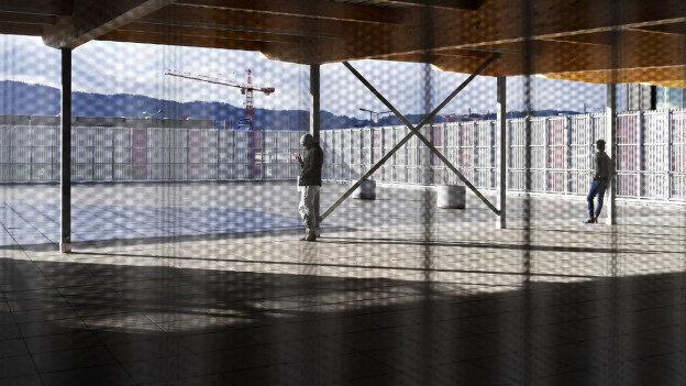 Ein Asylsuchender steht im neuen Bundesaslyzentrum und schaut in den Innenhof.