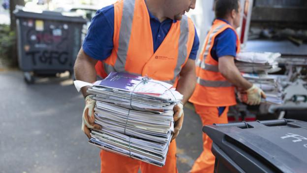 Kehrrichtmänner der Stadt Zürich sammeln Bündel von Altpapier ein.