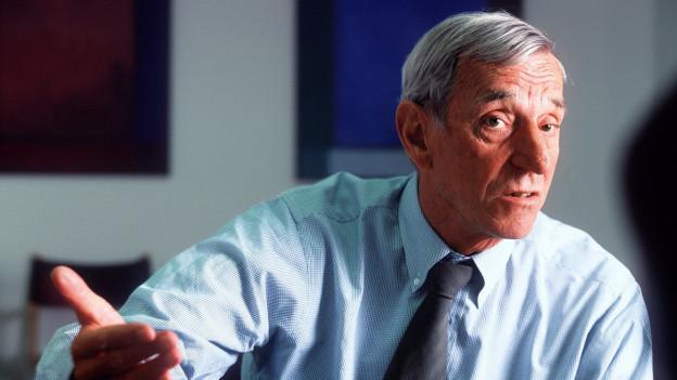 älterer Mann mit grauen Haaren und Kravatte gestikuliert