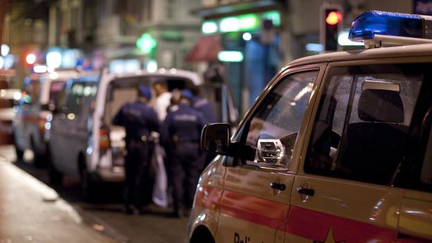 Ein Polizist nimmt in der Zürcher Langstrasse einen Mann fest.