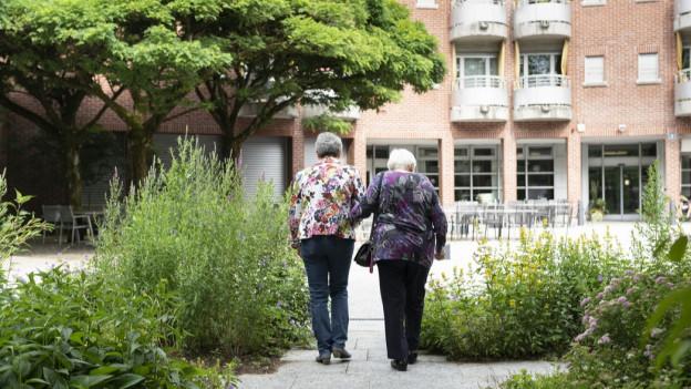 Zwei ältere Frauen laufen eingehakt auf den Eingang eines grossen, roséfarbenen Gebäudes zu.