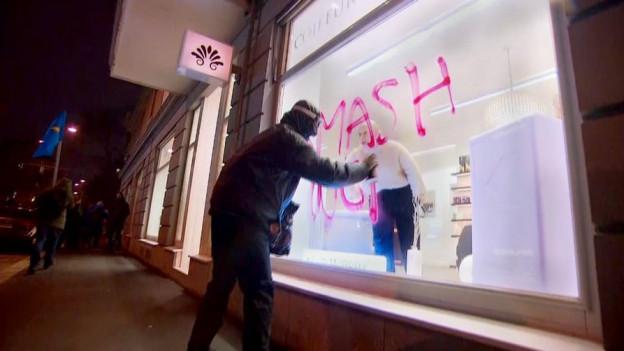 Ein Vermummter versprayt ein Schaufenster am Rande der Anti-WEF-Demonstration in Zürich.