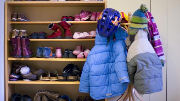 Kindergarderobe mit Schuhen, Jacken und Mützen