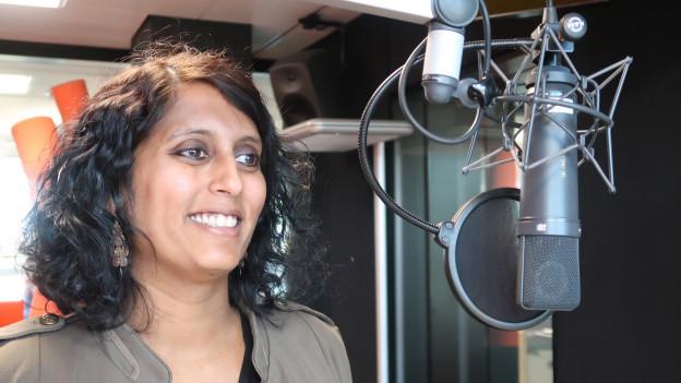 Eine Frau mit schwarzen Locken steht vor einem Mikrofon im Radiostudio.
